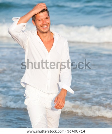 Portrait of cute happy smiling male walking carefree on the sunny coast thinking positive - stock photo