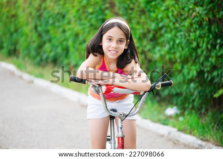 Portrait of cute hispanic girl on bicycle - stock photo