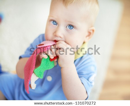 Portrait of cute infant playing with toy