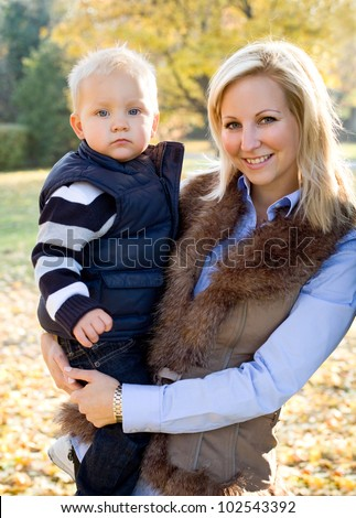 Portrait of cute kid and pretty mom having fun outdoors at fall. - stock photo
