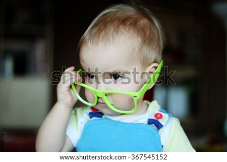 Portrait of cute kid boy with green eyeglasses holding glasses with hand and looking attentively, indoor portrait, educational concept - stock photo