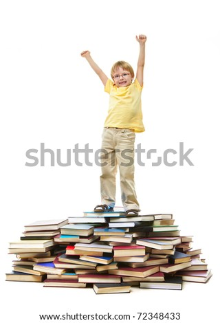 Portrait of cute kid standing on pile of books with raised arms - stock photo