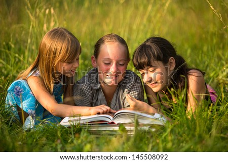Portrait of cute kids reading book in natural environment together. - stock photo