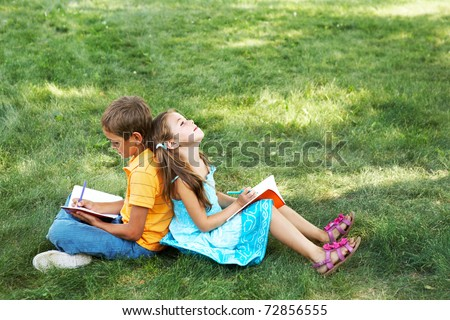 Portrait of cute kids seated on green grass with copybooks and pencils and drawing - stock photo