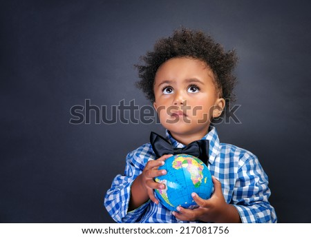 Portrait of cute little African boy holding in hands small globe on blackboard background, back to school concept - stock photo