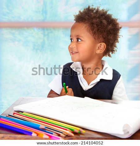 Portrait of cute little African preschooler on drawing lesson, painting with many colorful pencils, elementary education concept  - stock photo