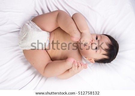 Portrait of cute Little asian boy 6 months old put his toe feet in the mouth on the white bed