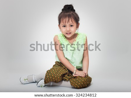 portrait of cute little asian girl wearing thai dress sitting by thai culture style (focus on face) - stock photo