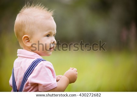 Portrait of cute little blond toddler boy looking into distance. Adorable child walking in the park on a sunny summer day. Summertime. Outdoors. Childhood and lifestyle concept. - stock photo