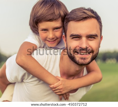 Portrait of cute little boy and his handsome young dad looking camera and smiling while resting in the park. Son is sitting pickaback - stock photo