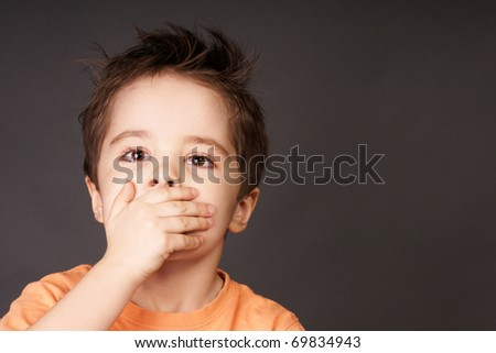 Portrait of cute little boy closed mouth with his hand, studio shot - stock photo