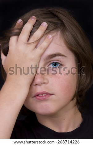 Portrait of cute little boy closed one eye with his hand. studio  - stock photo