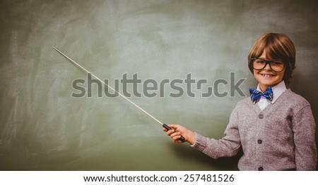 Portrait of cute little boy holding stick in front of blackboard - stock photo