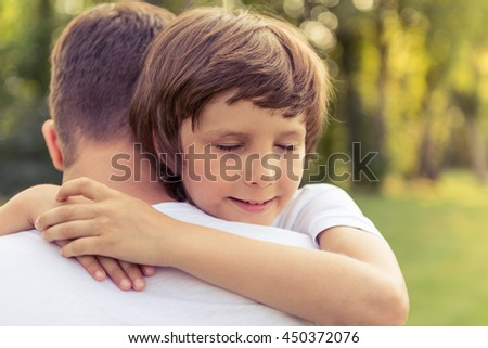 Portrait of cute little boy hugging his father while resting outdoors - stock photo