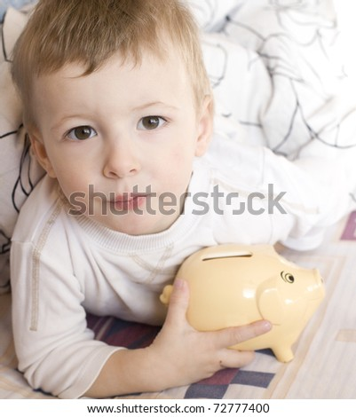 portrait of cute little boy in bed with piggy - stock photo