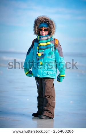 Portrait of cute little boy in winter clothes on beautiful winter day - stock photo