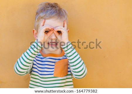 portrait of cute little boy making binoculars with his hands - stock photo