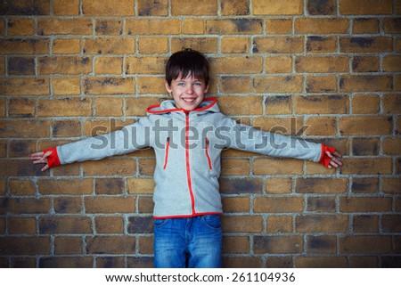 Portrait of cute little boy near brick wall outdoors - stock photo