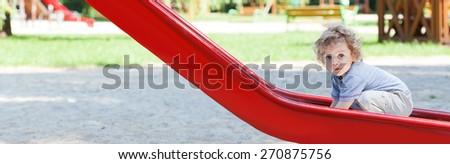 Portrait of cute little boy on slide - stock photo