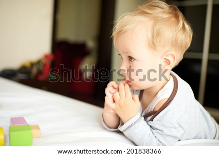 Portrait of cute little boy playing with blocks at home. - stock photo