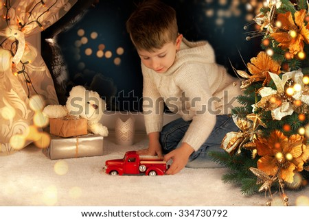 Portrait of cute little boy playing with Christmas light at home.