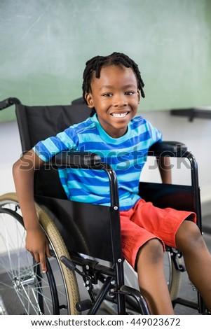 Portrait of cute little boy sitting on wheelchair in school - stock photo