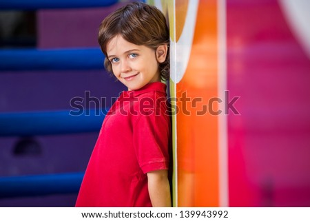 Portrait of cute little boy standing against wall in kindergarten