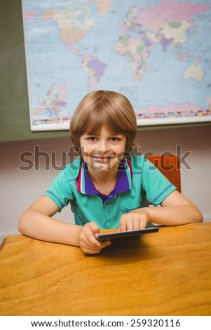 Portrait of cute little boy using digital tablet in the classroom - stock photo