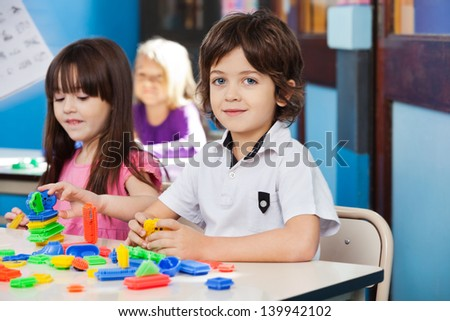 Portrait of cute little boy with blocks while friends playing in background - stock photo