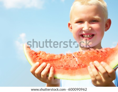 Portrait of cute little boyl with peace of red watermelon on blue sky background