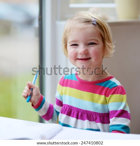 Portrait of cute little child, blonde preschooler girl holding felt-tip pen drawing on paper sitting at small table next to big window at home or kindergarten - stock photo