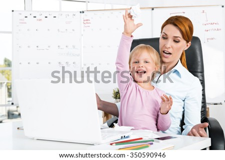 Portrait of cute little girl and her mother while working day. Business woman trying to amuse her daughter. Girl tearing paper and documents - stock photo