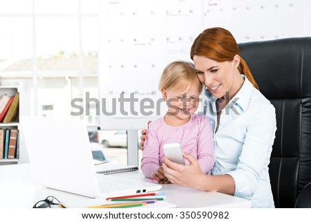 Portrait of cute little girl and her mother while working day. Business woman trying to amuse her daughter. Girl using mobile phone - stock photo