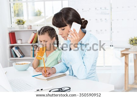 Portrait of cute little girl and her mother while working day. Business woman using mobile phone. Girl drinking juice - stock photo