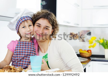 Portrait of cute little girl and mother in kitchen - stock photo