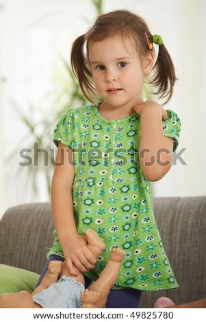 Portrait of cute little girl at home standing in living room, holding dolly. - stock photo