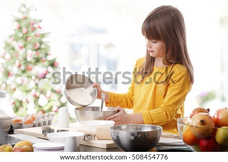 Portrait of cute little girl cooking at home at christmas time.