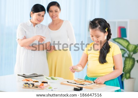 Portrait of cute little girl cooking sushi in the kitchen with her mother and grandmother on background - stock photo
