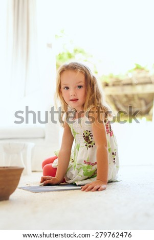 Portrait of cute little girl drawing while sitting on floor at home looking at camera. Elementary age young girl sitting in living room drawing. - stock photo