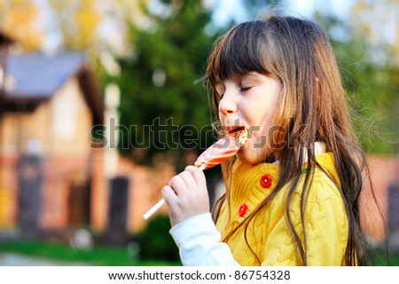 Portrait of cute little girl eating big lollipop on a stick outdoors - stock photo