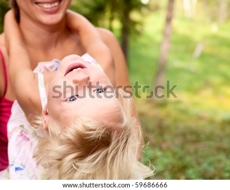 Portrait of cute little girl enjoying a summer day outdoors with her mom - stock photo