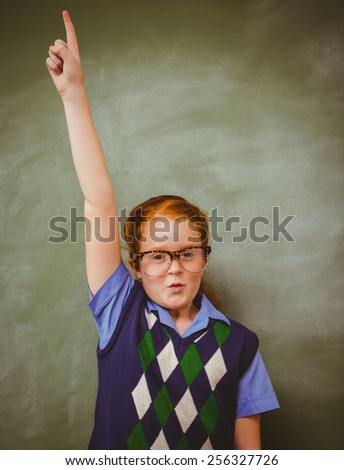 Portrait of cute little girl gesturing pointing upwards in the classroom - stock photo