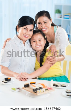 Portrait of cute little girl, her mother and grandmother sitting at the served table and looking at camera - stock photo
