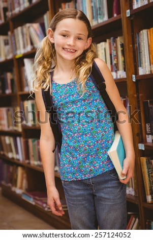 Portrait of cute little girl holding book in the library