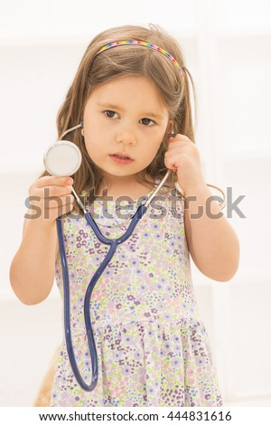 Portrait of cute little girl holding in her hand stethoscope playing doctor looking aside, indoor shot on white room.