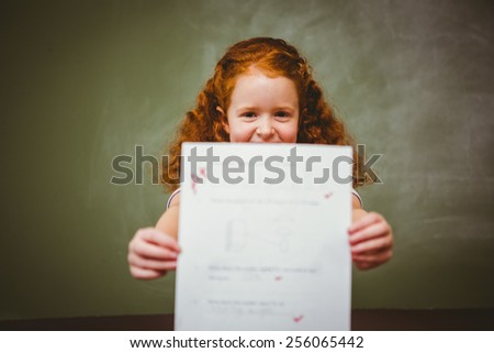 Portrait of cute little girl holding paper in the classroom