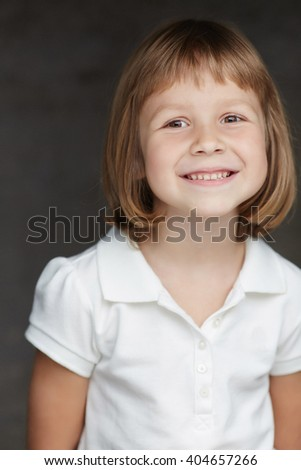 Portrait of cute little girl in a white shirt isolated on a dark grey background. - stock photo