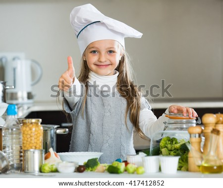 Portrait of cute little girl in cook cap cooking veggies - stock photo