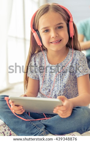 Portrait of cute little girl in headphones listening to music using a tablet, looking at camera and smiling while sitting on the floor - stock photo