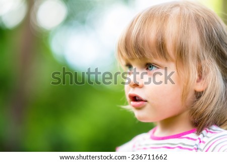 Portrait of cute little girl in nature. Side view, she is looking ahead at something or someone. Selective focus, shallow deep of field - stock photo